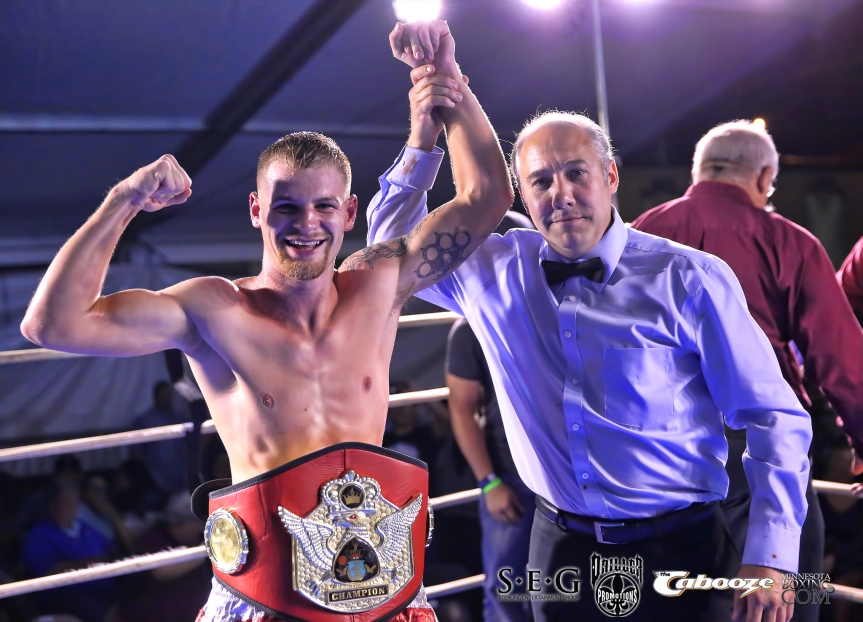 Brad Patraw with his hand raised by referee Mark Nelson after winning the MN State featherweight title on Friday night in Minneapolis.